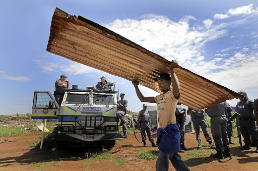 A squatter leaves after forced removals. The writer says the argument that debating the land question will divide society denies the reality that South Africa remains a deeply divided nation. /Halden Krog