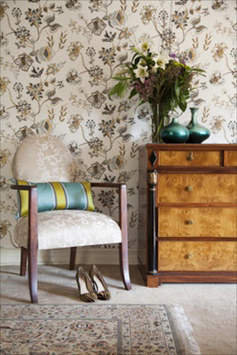 Gilded floral wallpaper adds a luxe touch to the feminine master bedroom.