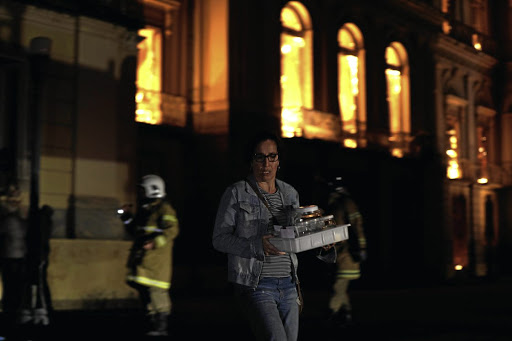 A worker rescues items as a fire rages at the National Museum of Brazil in Rio de Janeiro, on September 2 2018. Picture: REUTERS/RICARDO MORAES