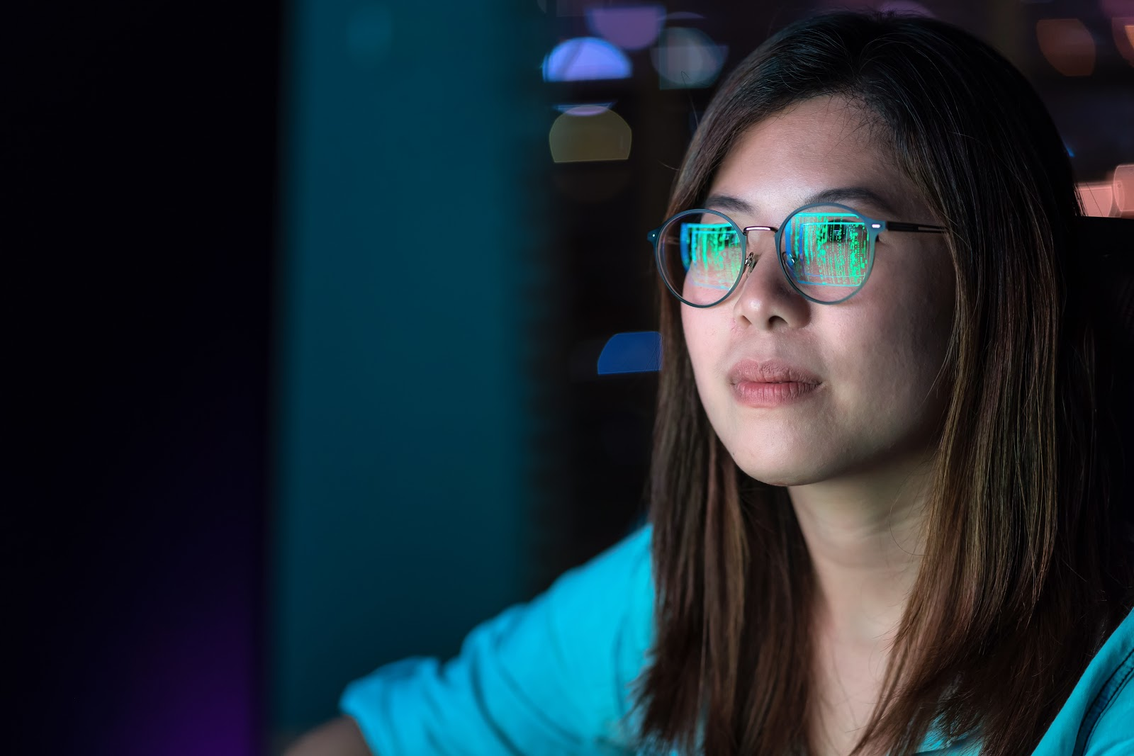 Young woman in a dark room staring at computer screen reflecting in her glasses
