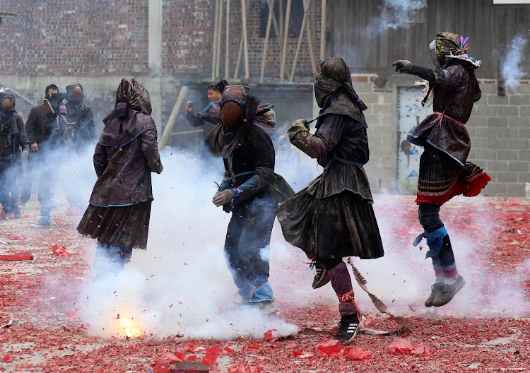 Villagers dressed as 'Maogao' jump next to firecrackers on the first day of the Chinese Lunar New Year of the Pig in China.