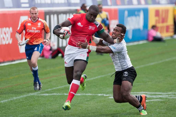 Kenya sevens captain Andrew Amode fends off Fijian playmaker Jerry Tuwai