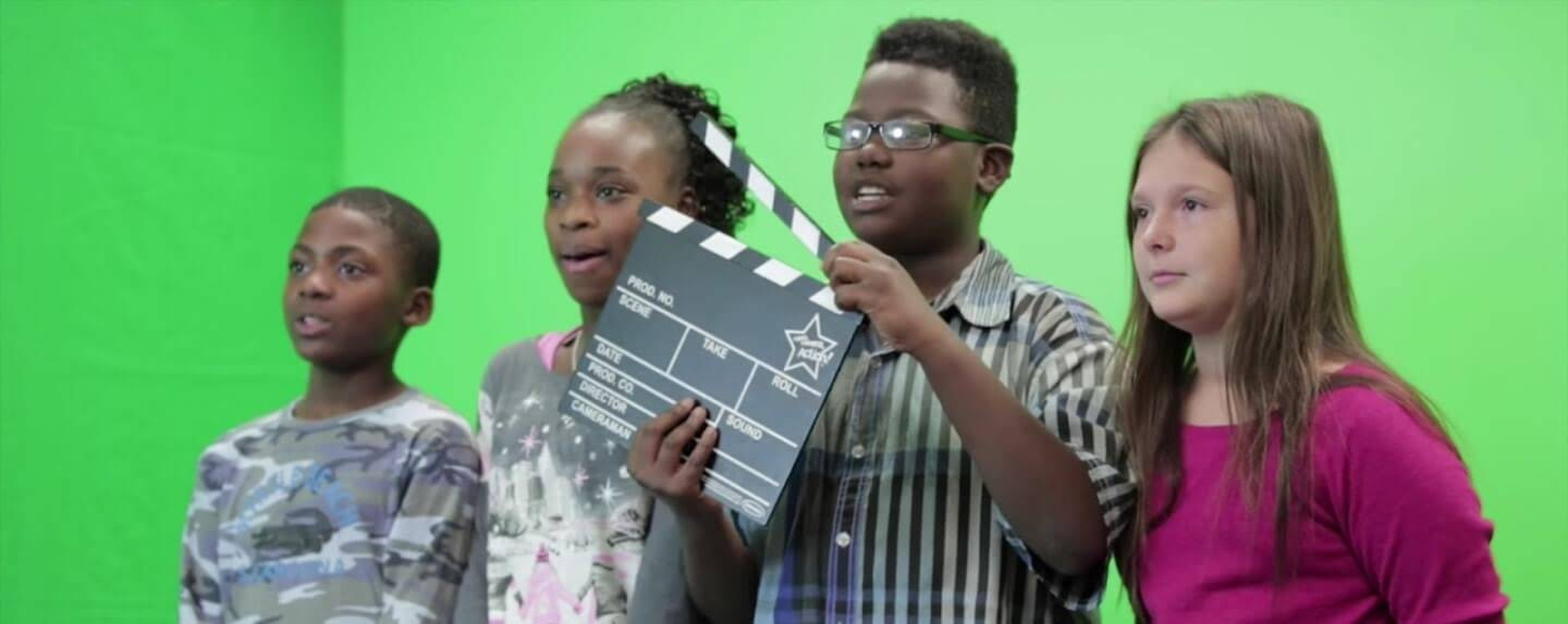 Kids in front of a green screen