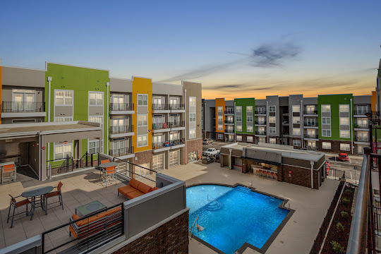 Community with green, orange, and tan exterior overlooking rooftop deck, pool, and community common area