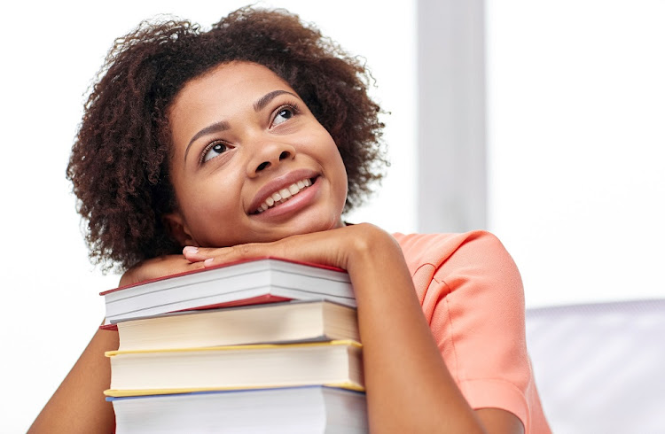A smiling student girl with books sitting at table.