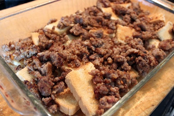 Bread arranged in a baking dish with crumbled sausage on top.