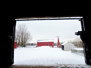 Photo: Red barn and windmill in the snow viewed from inside a barn at Carriage Hill Metropark in Dayton, Ohio.