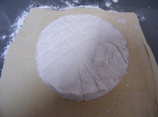 Working on a floured surface, roll out the puff pastry so it will fully...