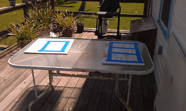 Photo: scrap plywood set up for practicing the application of Kiwi-Grip.  We placed one in the sun and one in the shade to experiment with drying times and textures.