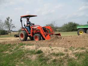 Photo: Ed Rains scooping up dirt after running the disk plow through to soften the dirt up.