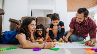 un hombre, una mujer y dos niños jugando juntos en el suelo