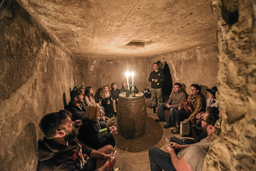Fascinating stories: Wine maker Philip Jonker, standing, presents wines at an underground tasting. After a lot of effort he made a fortified wine from old vines on Robben Island. Picture: SUPPLIED