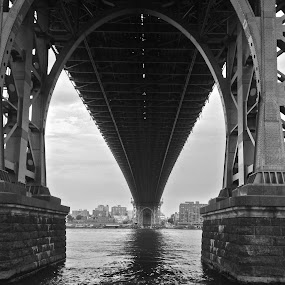 Under the Bridge B&W by Susan D'Angelo - Black & White Buildings & Architecture ( water, arch, brick, buildings, suspension, manhattan, architecture, bridge, brooklyn, span, city )