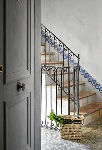 The stairwell features a cast-iron balustrade, stone treads, and Mallorcan wall tiles.