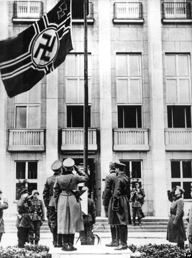 Радянські військовослужбовці разом із німцями віддають честь німецькому прапорові зі свастикою під час урочистостей у рамках військового параду. Брест-Литовський, 22 вересня 1939 року