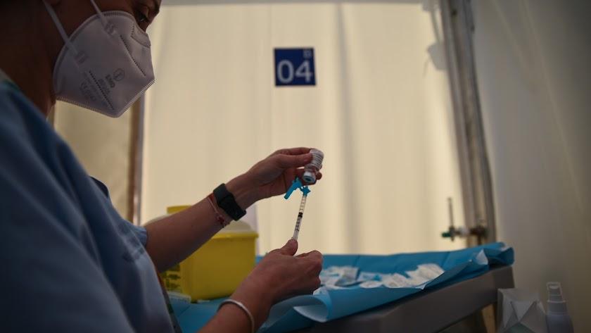 Una profesional sanitaria sostiene una jeringuilla y un vial con la vacuna contra la Covid-19.