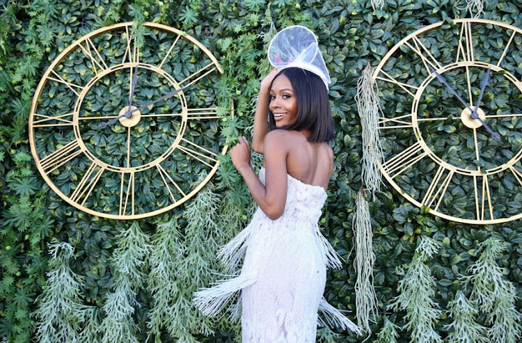 Zuri Hall from E entertainment wore a classy white dress and fascinator at The Vodacom Durban July.