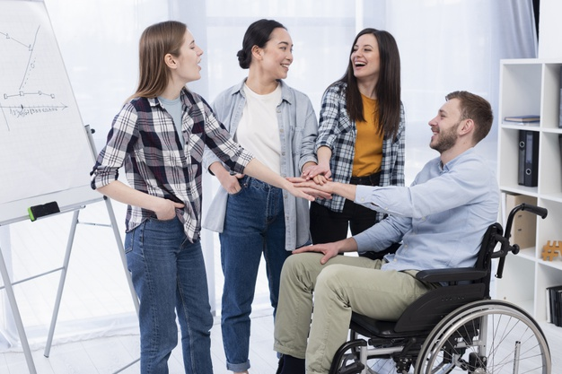Group of worker smiling in front of a whiteboard, one of them is using a wheelchair