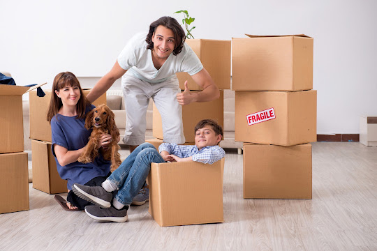 Stock photo of family with dog and boxes