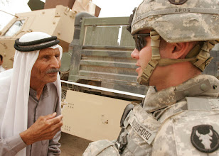 Photo: May 16, 2007,  AL MADINAH, Iraq,  Army Sergeant Jeff Woodford a Walker, Minnesota native speaks to an Iraqi civilian waiting for medical care. Citizens of Al Madinah As Siyahiyah take advantage of the medical care being provided by soldiers from 1st Iraqi Army Division running a Cooperative Medical Engagement (CME) with the help of Able Company, 2nd Combined Arms Battalion of the 136th Infantry Regiment, 2nd Marine Logistics Group (Forward). Sgt Woodford is a medic with A. co., 2-136th CAB. 2nd MLG is deployed within the Al Anbar province in order to develop the Iraqi Security Forces, facilitate the development of official rule of law through democratic government reforms and continue the development of a market based economy centered on Iraqi reconstruction.