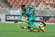 Baroka FC midfielder and captain Mdududzi Mdantsane slides away from a challenge by Danny Phiri of Golden Arrows during an Absa Premiership match at New Peter Mokaba Stadium in Polokwane on March 13, 2019.