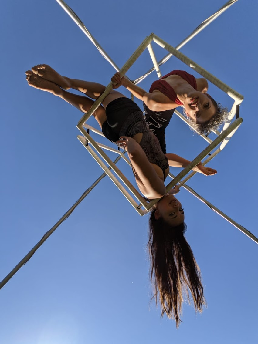 Photo looking up at two girls practicing trapeze. Captured on Pixel.
