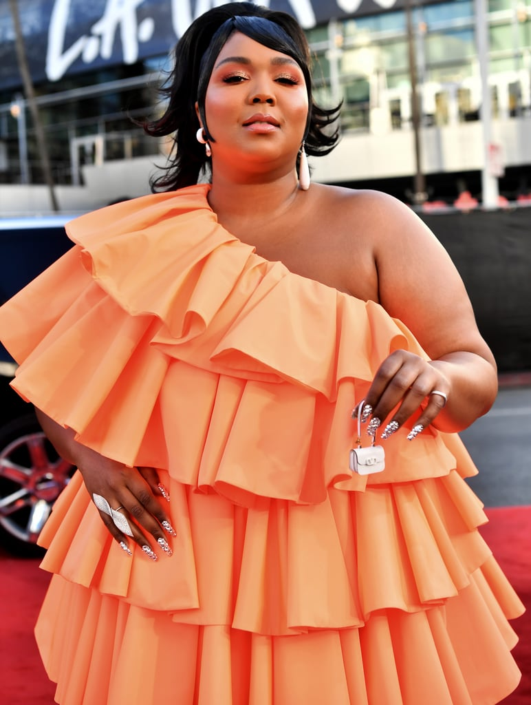 Large black woman wearing a one shouldered orange dress with several ruffled tiers and the tiniest purse ever.