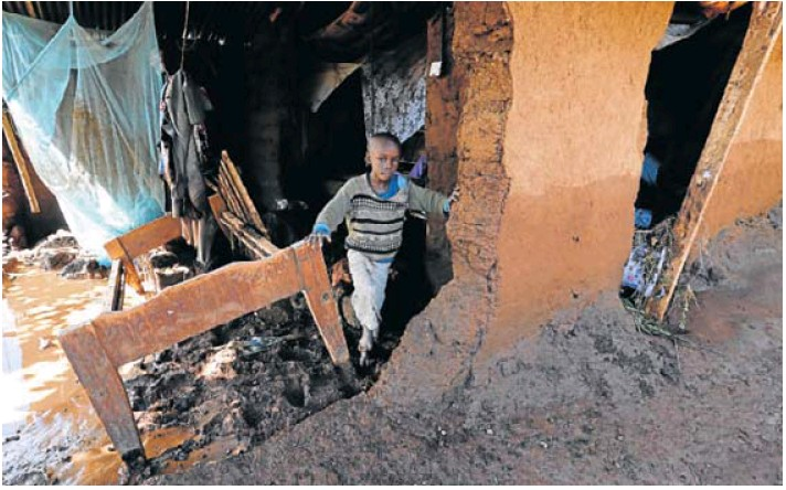 A child in a house damaged by flooding after the dam burst in Solai