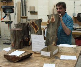 Photo: Tim Aley adds perspective to some nice cedar and cherry at the Silent Auction table.