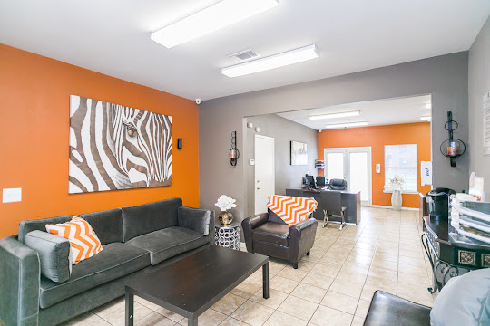 Clubhouse with orange and grey walls, tile floors, plush seating, desk with chairs, coffee bar