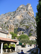 Photo: By early afternoon, we arrive at the picturesque cliffside village of Moustiers-Sainte-Marie. The town is most renowned for its faience, the glazed earthenware produced here since the 17th century (when a monk brought the secrets of the glazing from the Italian town of Faenza - hence the name). The upper part of the four-level Lombard Romanesque (Italianate) bell tower of the 12th-century Notre-Dame church (restored in 1928) can be seen at center left.