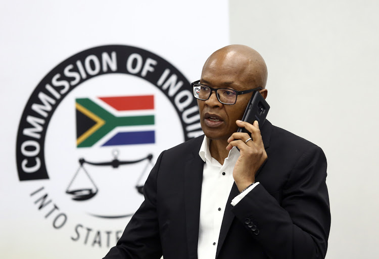 Mzwanele Manyi talks on his phone at the state capture inquiry in Parktown, Johannesburg, on November 14 2018.