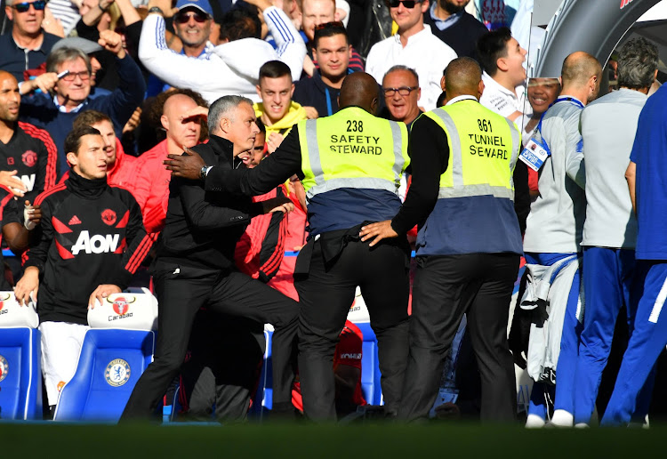Manchester United manager Jose Mourinho is restrained by stewards after reacting to Chelsea's second goal.