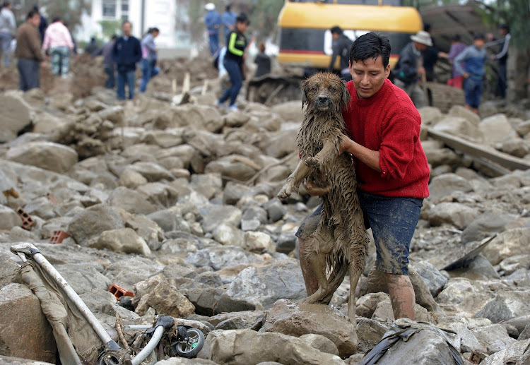 A man carries a dog from mud and stones after a river flooded Tiquipaya, Bolivia, due to heavy rains.