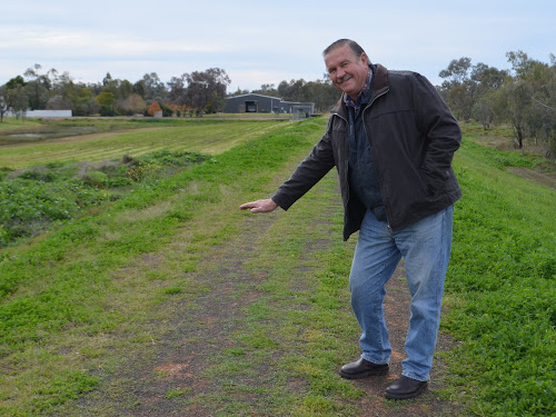 Cr Ron Lowder indicates the anticipated extra height of the augmented flood levee. Design work will soon get underway.