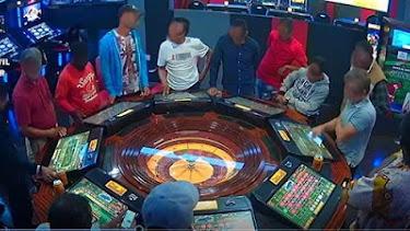 Hombres juegan a la ruleta en un salón de juego.