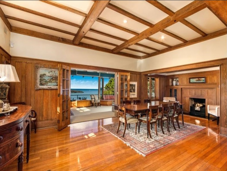 A stately dining room features polished wooden floors and a fireplace.