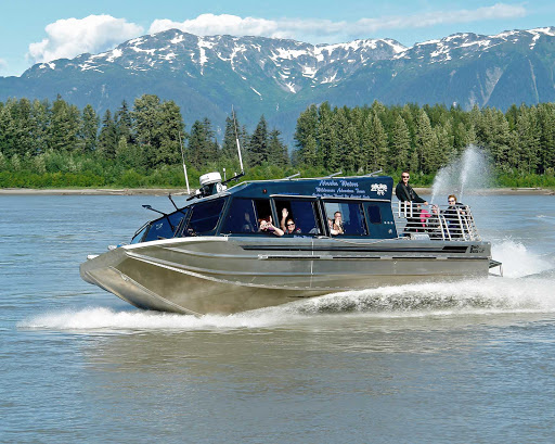 Stikine-Jet-Boat.jpg - Explore the Stikine River in southeast Alaska on a jet boat ride, offering beautiful views of snow-capped mountains and lush riverbanks, during an American Cruise Lines voyage.
