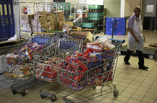 Damage done: A worker walks past polony products after they were removed from the shelves of a Pick n Pay outlet in Johannesburg. The strain responsible for 90% of cases of listeria infection was traced to polony made in a Tiger Brands factory in Polokwane. Picture: REUTERS