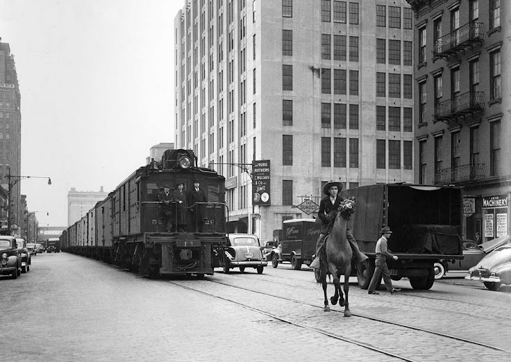 "A ""West Side Cowboy"" rides ahead of the train running along ""Death Avenue."""