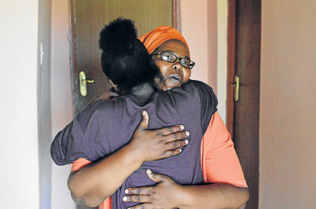 Khayakazi Mabona hugs her daughter, Saphetha, at their home in Peddie after checking out a highly suspicious work contract from Uganda.