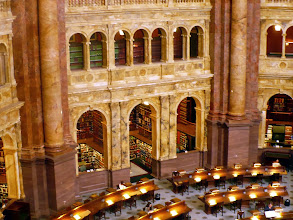 Photo: Desks and an alcove of reference books in the main reading room of the Library of Congress.