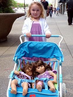 Little girl pushing two dolls in twin doll stroller
