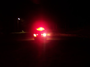 Photo: Firefighter standing in front of apparatus with lightbar on is obscured to oncoming vehicles.