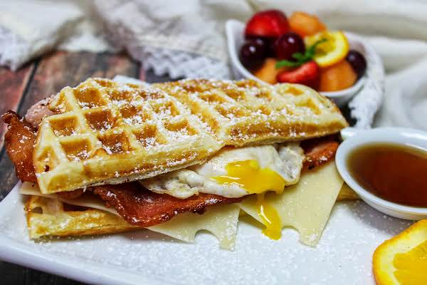 Easter Waffle Breakfast Sandwich With The Yolk Broken On A Plate.