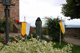 Photo: Udenfor kirken en statue af Hildegard med paveflagene