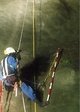 Photo:    深夜の鉄道法面      ロープと平行な黄色いテープ上のものは巻尺。