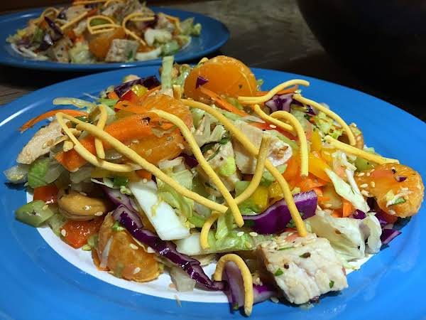 A Plate Of Salad With Segments Of Mandarin Oranges And Crispy Chow Mein Noodles.