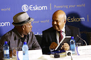 Eskom chairperson Jabu Mabuza talks to Minister of Public Enterprise Pravin Gordhan before a media briefing on December 6 2018 about the power outages that have hit the country.