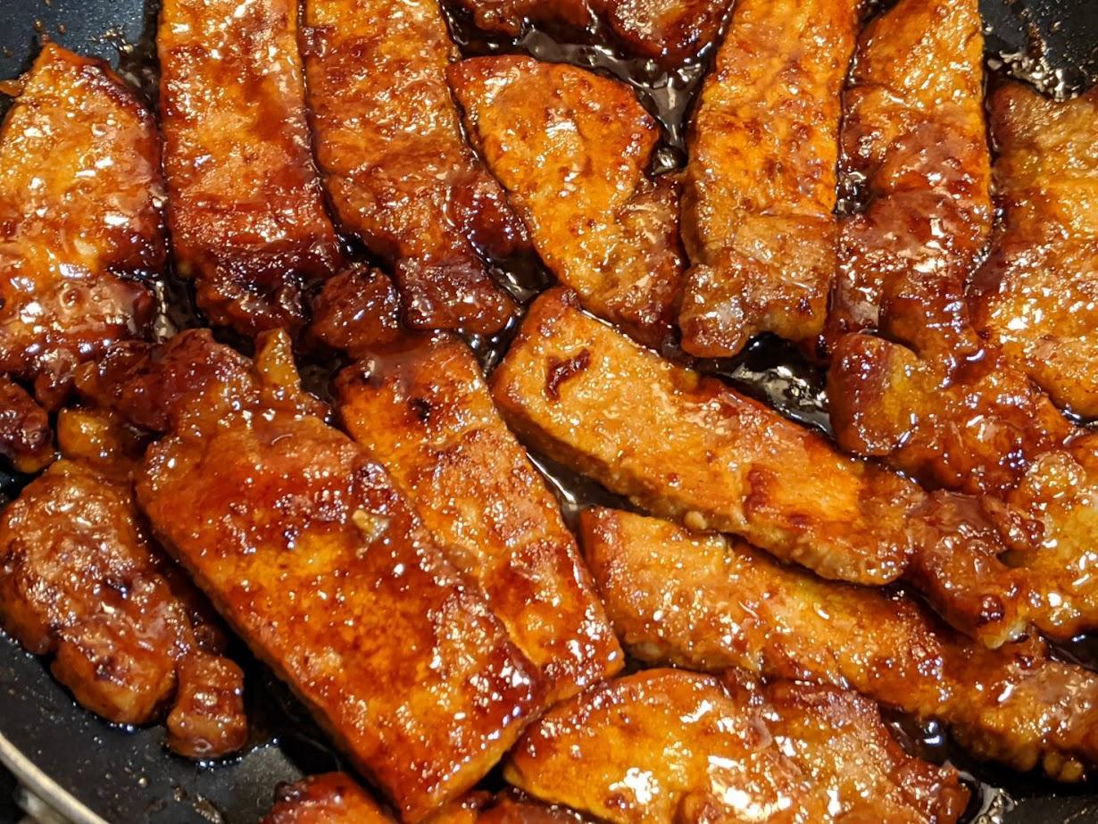 焼いた豚肉にソースを絡めているところ